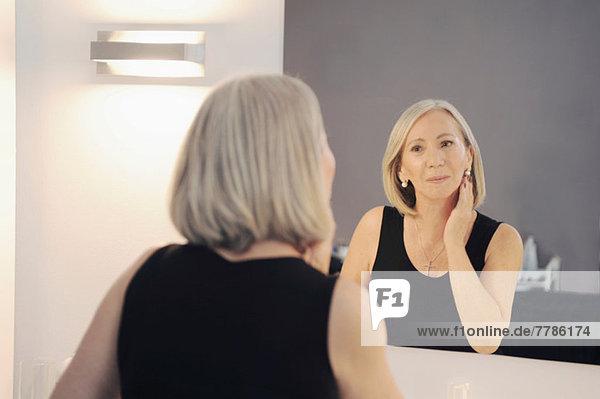 Seniorenfrau  die sich im Spiegel spiegelt