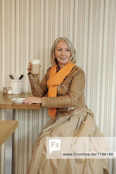 Seniorin auf dem Coffee Shop sitzend