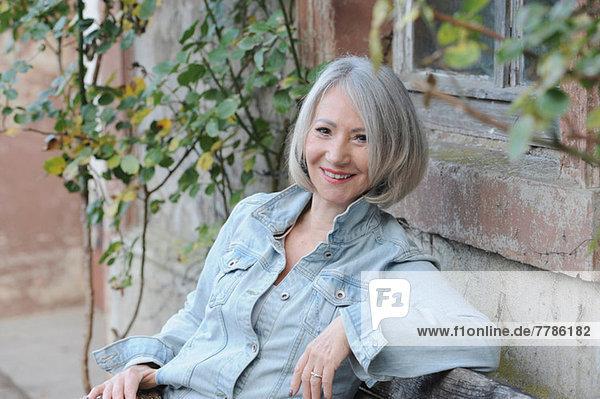 Porträt einer älteren Frau  die sich im Garten entspannt.