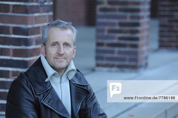 Porträt eines reifen Mannes auf einer Treppe sitzend