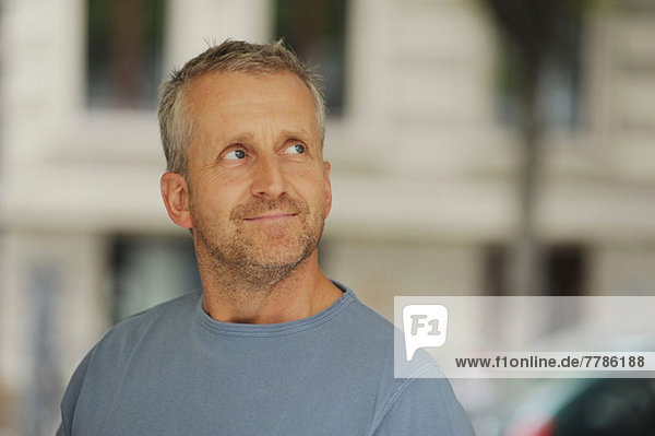 Erwachsener Mann schaut weg und lächelt  drinnen