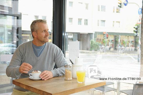 Erwachsener Mann im Coffee-Shop sitzend