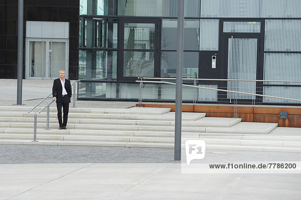 Erwachsener Mann steht vor dem Bürogebäude