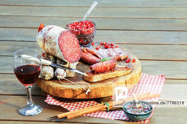 Salami auf Schneidebrett mit Wein und Gewürzen