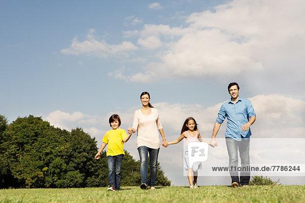 Familie mit zwei Kindern beim Händchenhalten  Spazierengehen