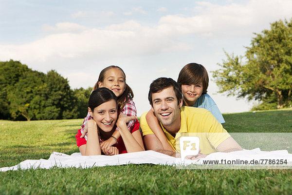 Porträt einer Familie mit zwei Kindern auf Gras liegend