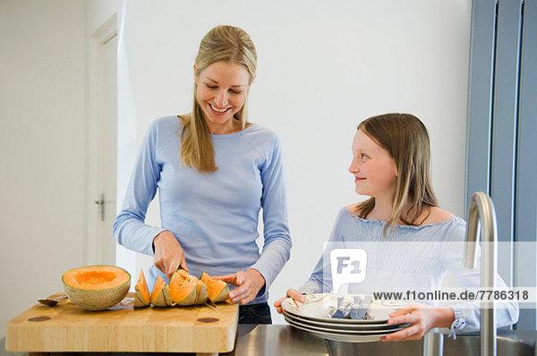 Mutter und Tochter bei der Zubereitung der Melone