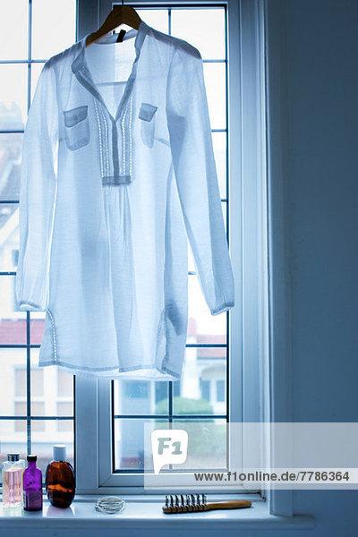 Bluse im Fenster hängend