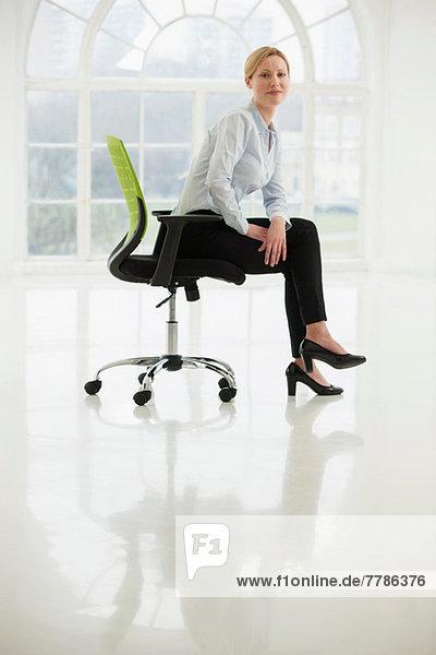 Geschäftsfrau sitzt auf einem Bürostuhl im kargen weißen Raum