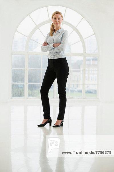 Geschäftsfrau im kargen weißen Raum stehend