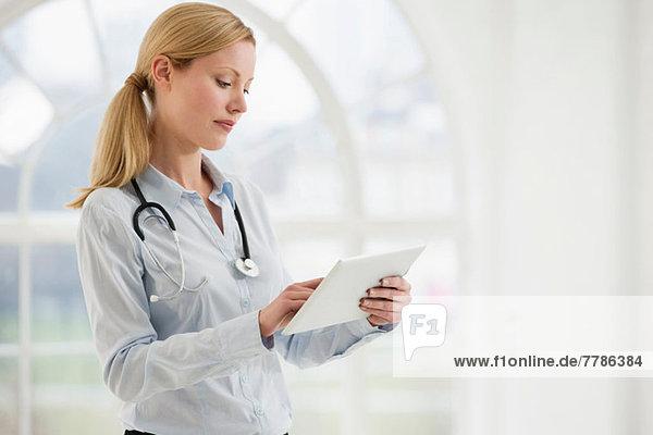 Porträt einer Ärztin mit Stethoskop und digitalem Tablett