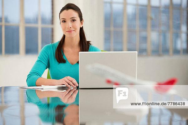 Büroangestellte am Schreibtisch sitzend mit Laptop