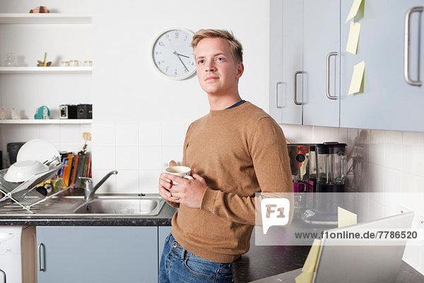 Junger Mann in der Küche mit Kaffeetasse