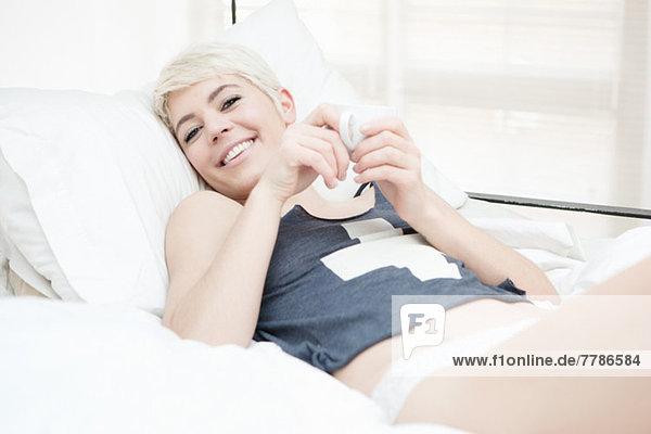 Frau auf dem Bett liegend mit Teetasse