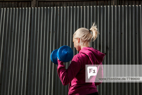 Junge Frau mit Handgewichten beim Bauen