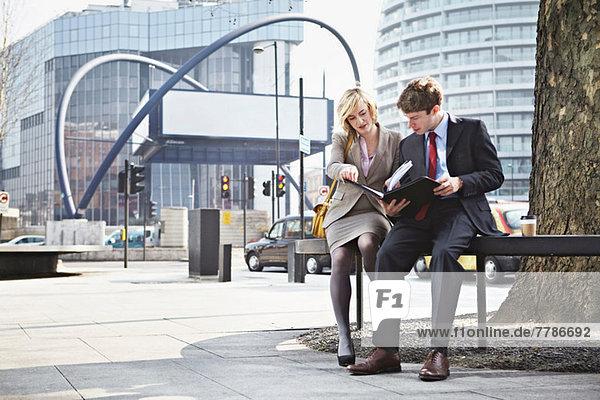 Zwei Geschäftsleute  die in der Stadt auf dem Geländer sitzen.