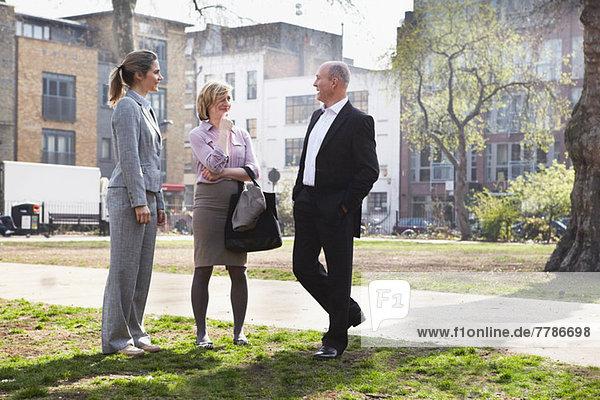 Drei Geschäftsleute  die im Park stehen und reden.