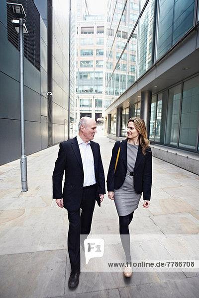 Geschäftsmann und Geschäftsfrau beim Vorbeigehen an Bürogebäuden