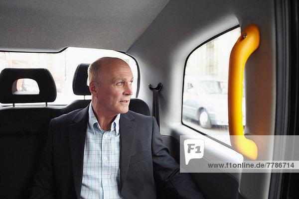 Mature businessman in black cab  London  England  UK