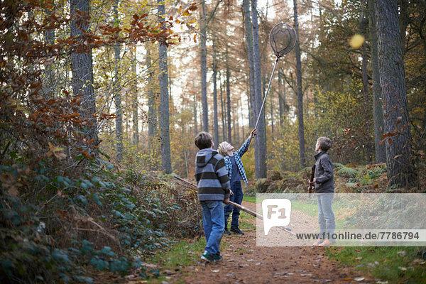 Jungen beim Waldspaziergang mit Angelausrüstung