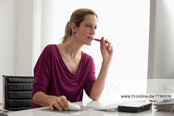 Woman using computer mouse  biting pen