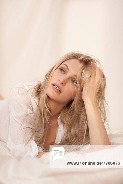 Nahaufnahme einer jungen blonden Frau auf dem Bett liegend