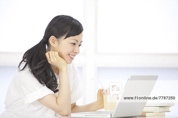 Young Frau blickt auf laptop