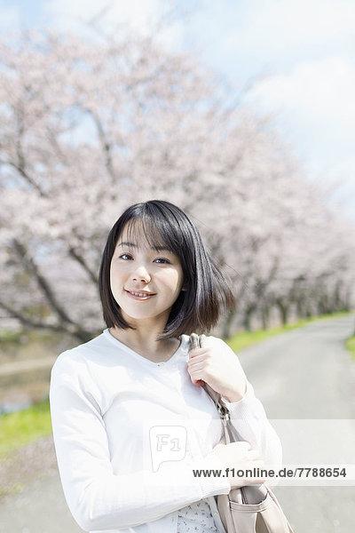 Junge Frau stützt Kopf auf Hand  Porträt vor weißem Hintergrund