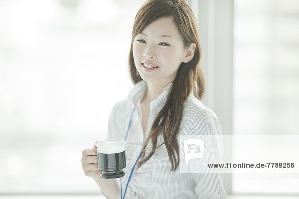 Young Businesswoman Holding Coffee By the Window