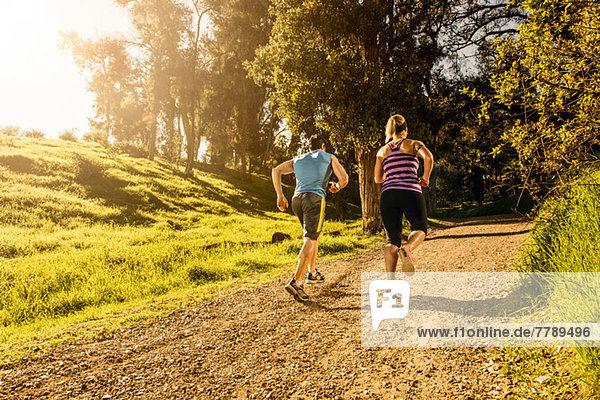 Zwei Personen joggen auf dem Waldweg