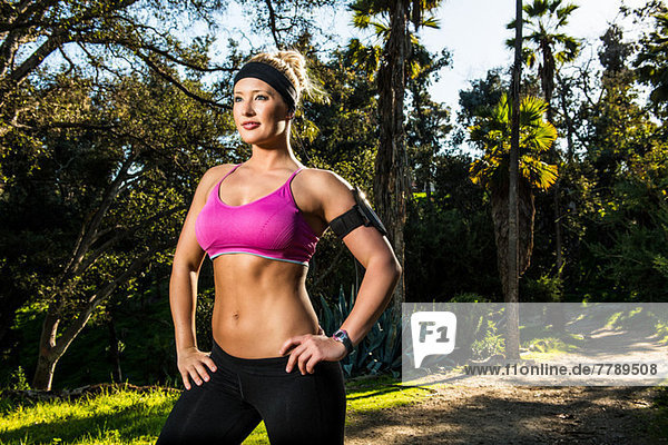 Young woman exercising in forest resting with hands on hips