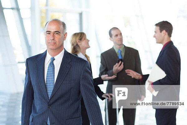 Ausgebildeter Geschäftsmann mit Kollegen im Hintergrund