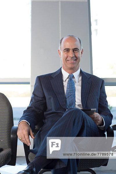 Mature businessman sitting in chair