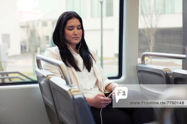 Junge Frau im leichten Zug mit Kopfhörer