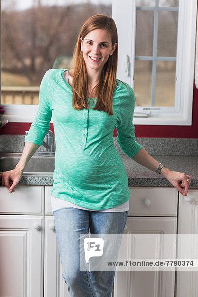Porträt einer schwangeren Frau in der Küche