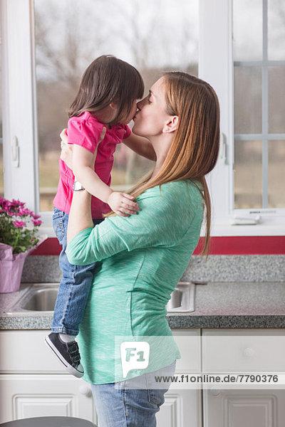 Schwangere Mutter mit Kleinkind Tochter in der Küche
