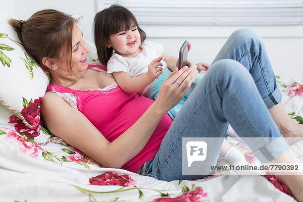 Porträt einer schwangeren Frau und einer Kleinkind-Tochter  die auf dem Bett liegt und mit dem Smartphone spielt.