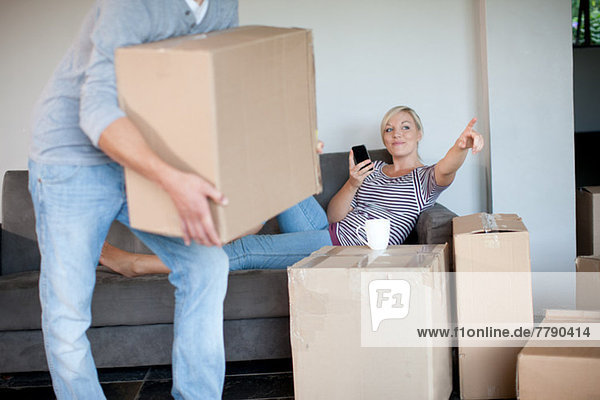 Junge Frau bewegt Haus auf Sofa Regie Mann mit Box