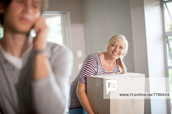 Junge Frau beim Umzug mit Kiste