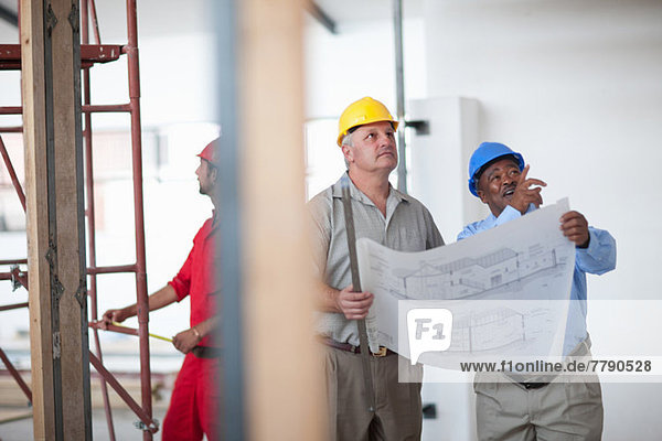 Construction workers pointing and looking with blueprint on construction site