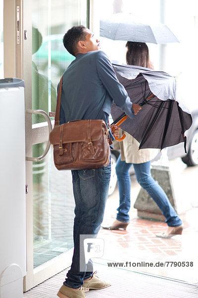 Junger Mann in der Tür mit Regenschirm