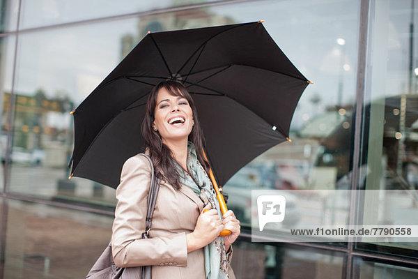 Mittlere erwachsene Frau mit Regenschirm