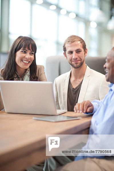 Geschäftsmann mit Laptop und Kollegen