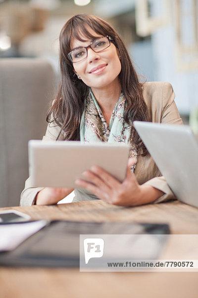 Mittlere erwachsene Geschäftsfrau mit digitalem Tablett