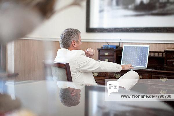 Lässiger Geschäftsmann im Hotelzimmer mit Laptop