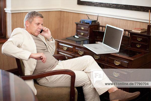 Erwachsener Mann auf dem Handy am Schreibtisch sitzend