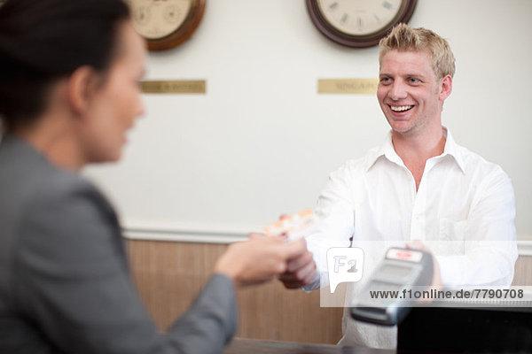 Frau bezahlt jungen Mann an der Hotelrezeption