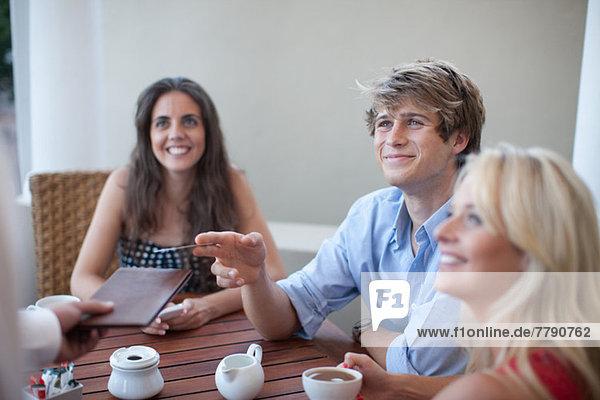 Junge Erwachsene bestellen im Cafe