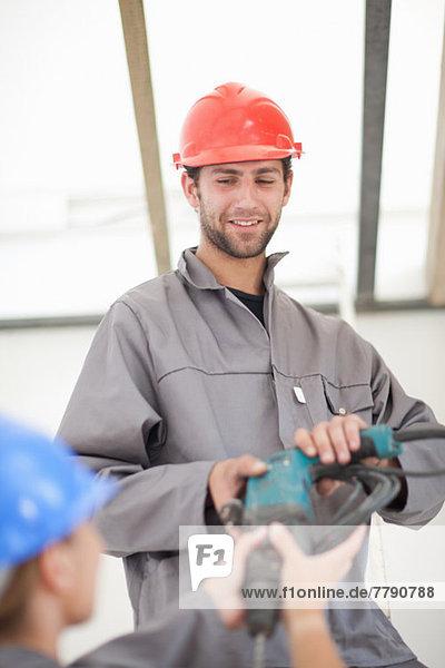 Arbeiter und Arbeiterinnen bei der Handarbeit auf der Baustelle