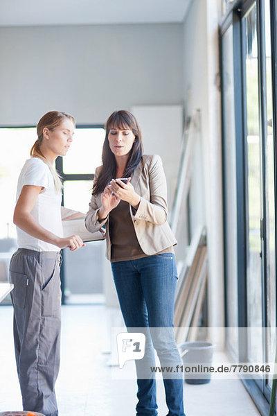 Interior designer and laborer looking at smartphone